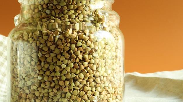 Зеленые ростки сырой органической гречки в стеклянной банке для круп. концепция веганской еды. органическая еда. понятие о диете, похудании, здоровом и правильном питании. скопируйте место для текста.