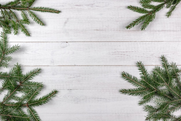 흰색 나무 바탕에 프레임으로 녹색 가문비 나무 가지. 복사 공간 크리스마스 컨셉
