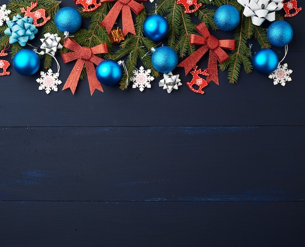 Green spruce branches, christmas blue and pink balls, red shiny bows