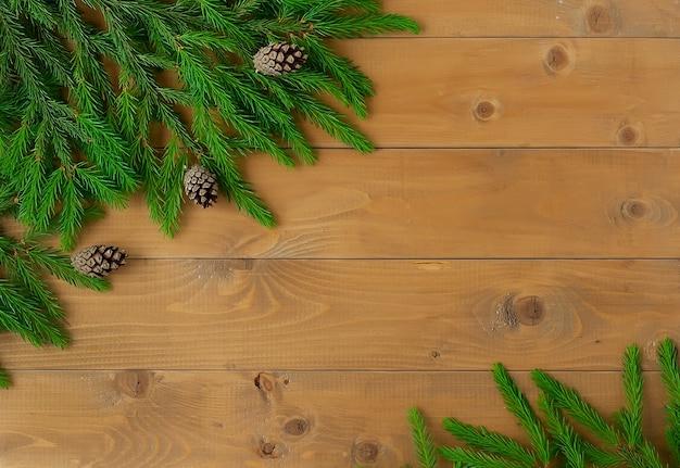 明るい木の背景に緑のトウヒの枝。板で作られた木製のテーブルの上の偽の人工トウヒの枝。