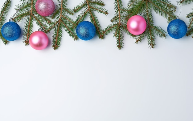 Green spruce branches and pink and blue shiny christmas balls
