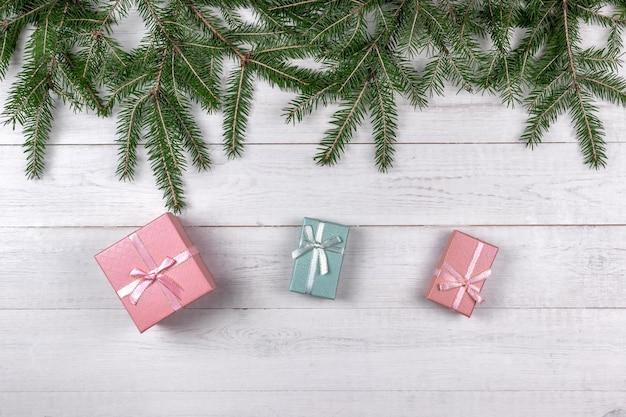 Green spruce branches and pink gift boxes on white wooden background. christmas concept with copy space