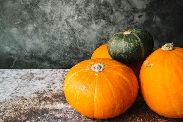 Green squash on orange pumpkins