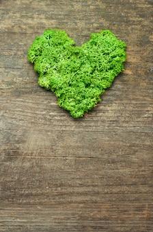 텍스트에 대 한 빈 공간을 가진 소박한 나무 배경에 심장 모양의 녹색 안정화 이끼