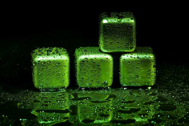Green stainless steel cubes simulating ice for cooling drinks on a black surface with a reflection.