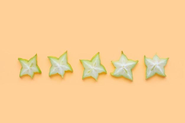 黄色のパステルカラーの表面に緑色の星の果実のスライス