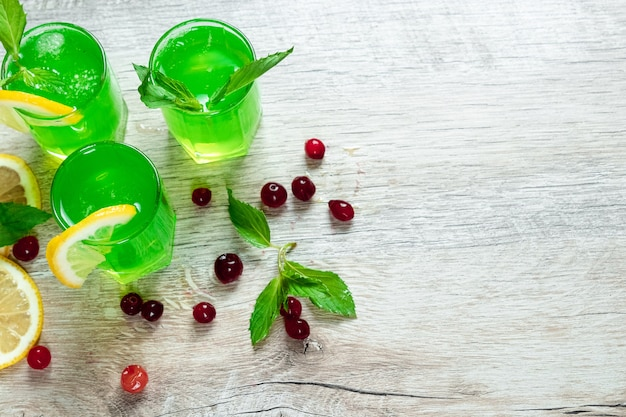 Green stemware shot alcoholic cold cocktail with cranberries raspberries lemon and mint