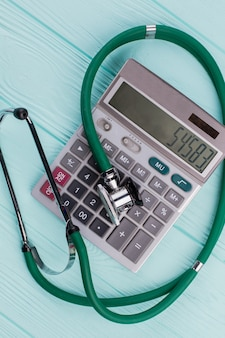 Green stethoscope on calculator. concept cost of healthcare.