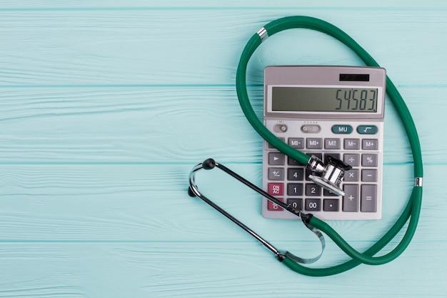Green stethoscope near calculator on the blue wooden desk. grey big calculator.