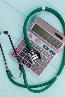 Зеленый стетоскоп на калькуляторе. понятие стоимости здравоохранения.