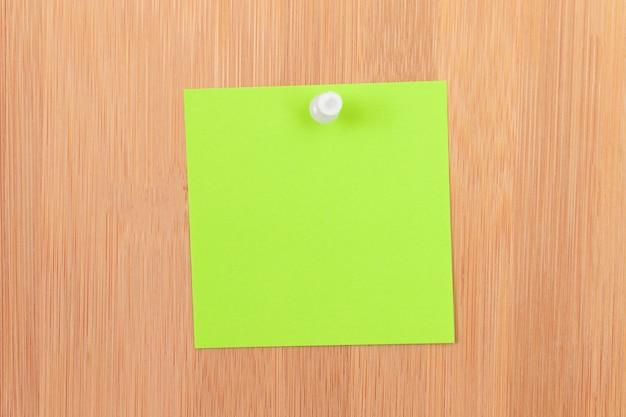 나무 메시지 보드에 고정된 녹색 스티커 메모