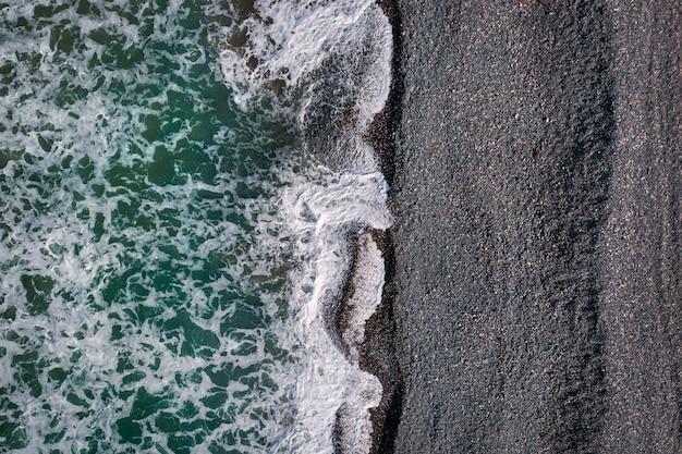 검은 모래 해변에서 바다 거품이 부서지는 녹색 폭풍우 치는 파도, 바로 위의 바다 질감 보기
