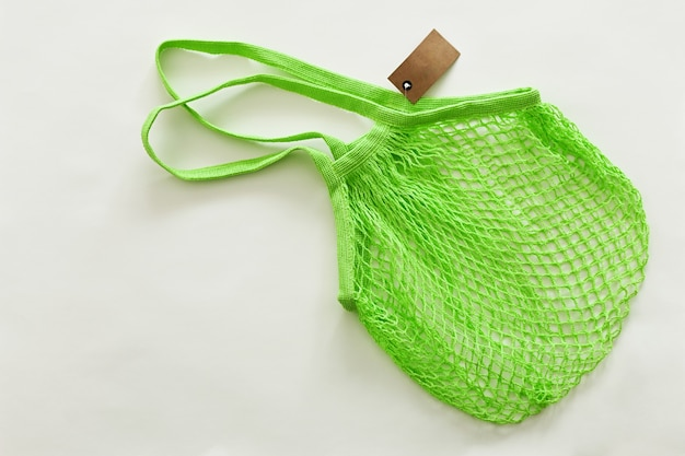 白い背景の上の食品のための緑のストリングバッグ