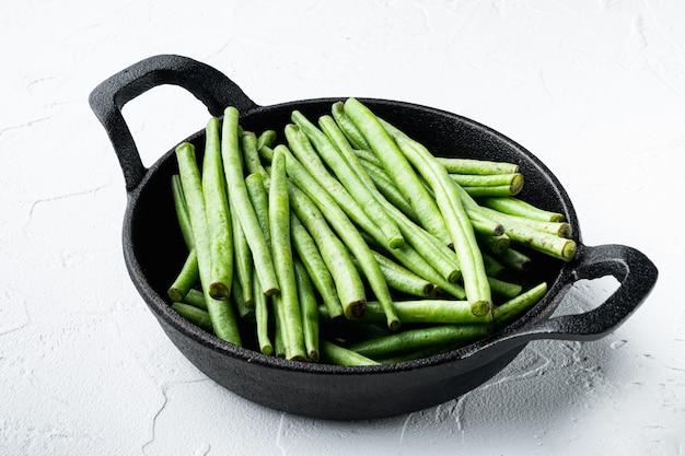흰색 돌 배경에 튀김 주철 팬에 녹색 끈 콩 세트 프리미엄 사진