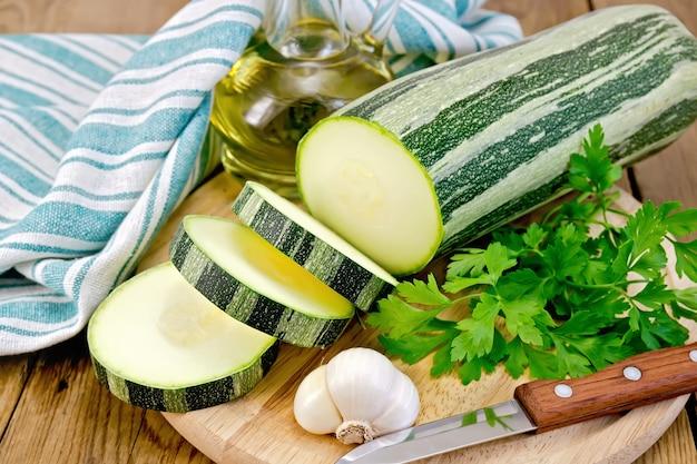 緑の縞模様のズッキーニ、ニンニク、植物油のボトル、パセリ、緑のナプキン、木の板の背景にナイフ
