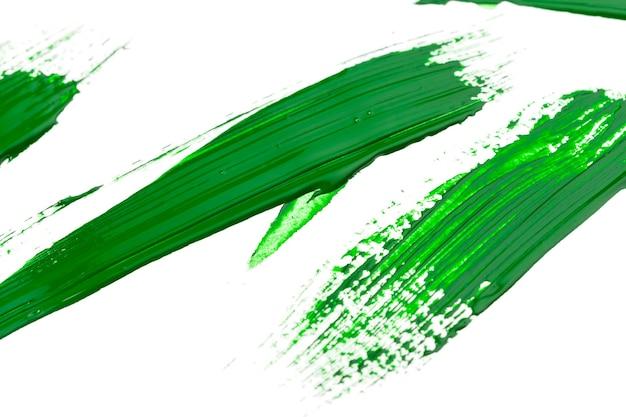 Green stroke of the paint brush on white paper