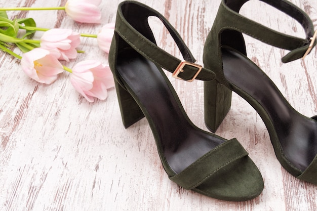 Green suede shoes on a wooden background, pink tulips. fashionable concept