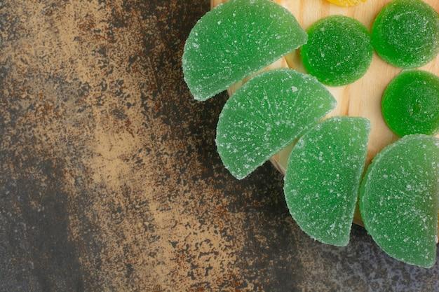Сладкий мармелад зеленого сахара на деревянной тарелке. фото высокого качества