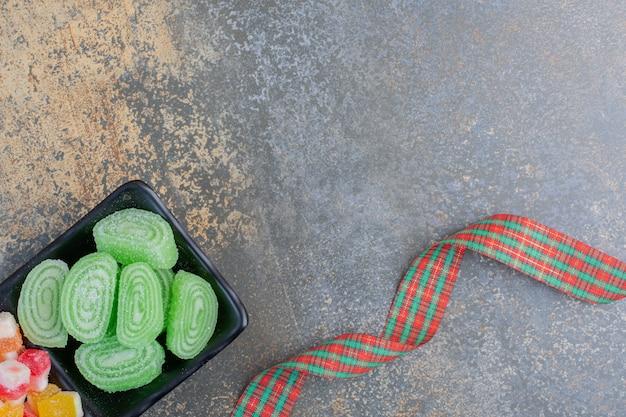 Caramelle di gelatina zuccherate verdi con fiocco festivo. foto di alta qualità