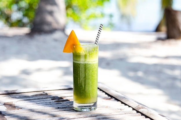 Green summer drink cocktail with mango on beach