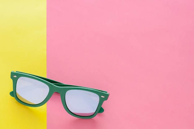 Green sunglasses isolated on colorful background for summer time.