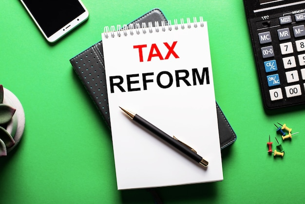 On a green surface  a telephone, a calculator and a diary with the inscription tax reform