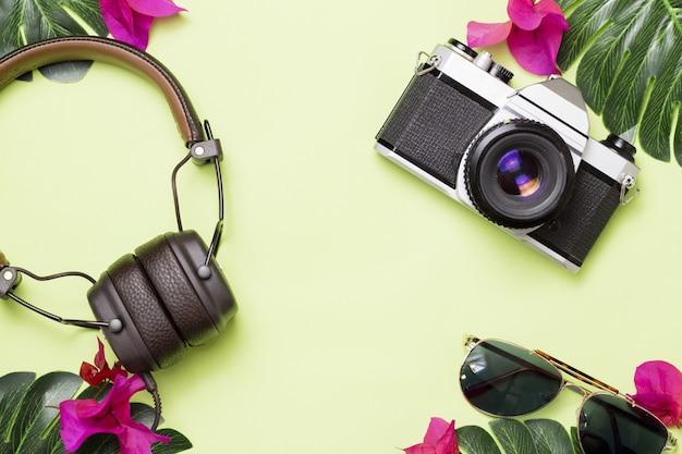 Superficie verde con fotocamera retrò, cuffie e occhiali con fiori tropicali