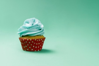 Green surface with tasty cupcake