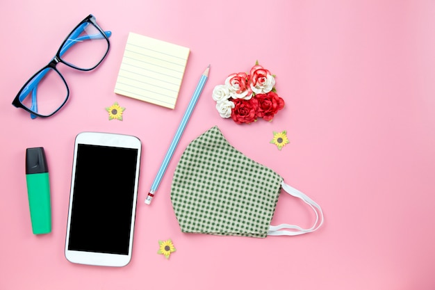 Green surgical mask plaid and blue glasses with pencil mobile clipping path screenflower on pink backgroud pastel style flatlay topview copyspace