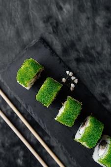 Green sushi set close-up on black surface