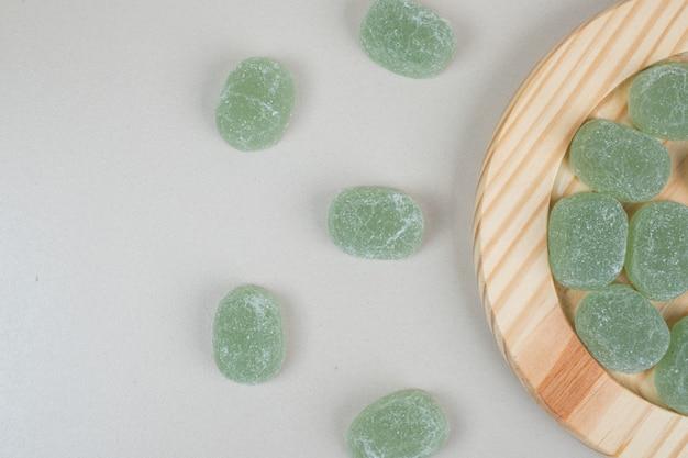 Caramelle di gelatina dolce verde su piatti di legno