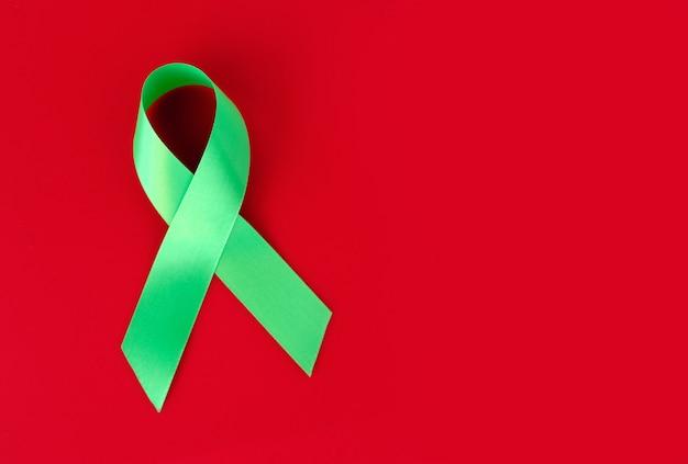 Зеленая символическая лента на красной поверхности