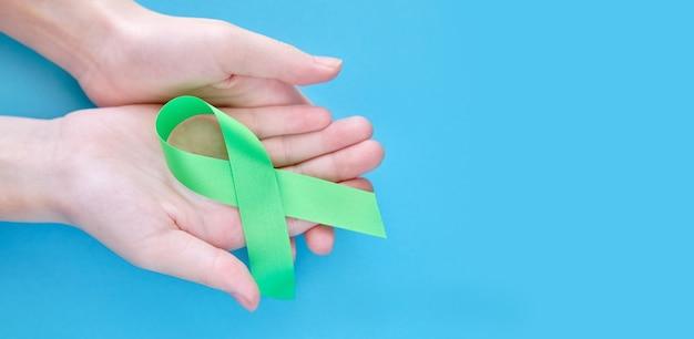 Зеленая символическая лента на руках женщины на белой поверхности