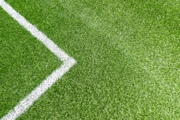Green synthetic artificial grass soccer sports field with white corner stripe line