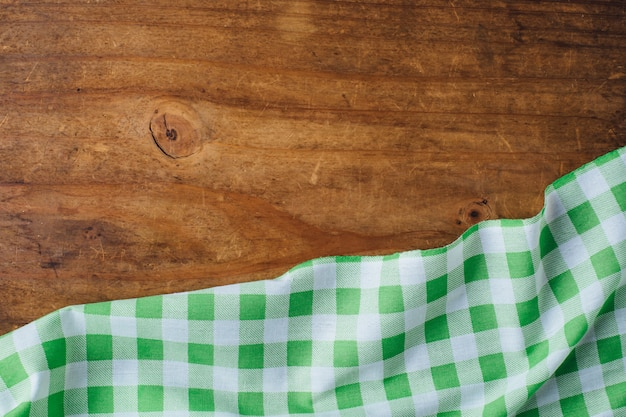 Green table cloth on wooden background