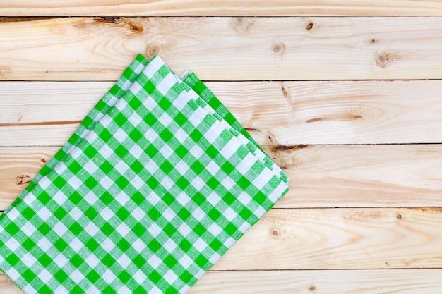 Зеленая скатерть на деревянном столе, вид сверху