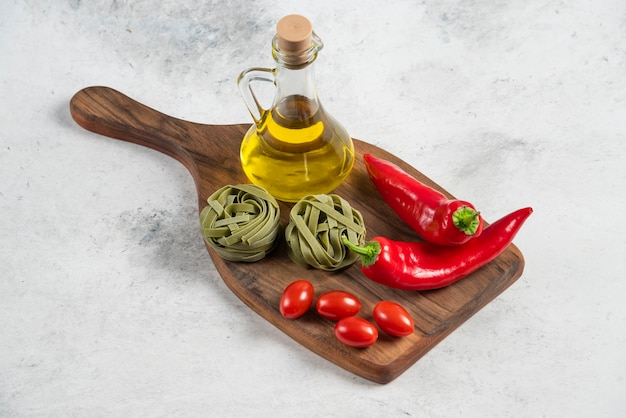 Tagliatelle verdi, verdure e olio d'oliva su tavola di legno.