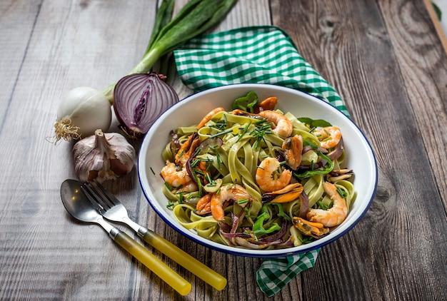 Green tagliatelle with seafood. mussels; prawns