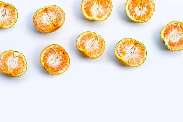 Green tangerines mandarines on white background.
