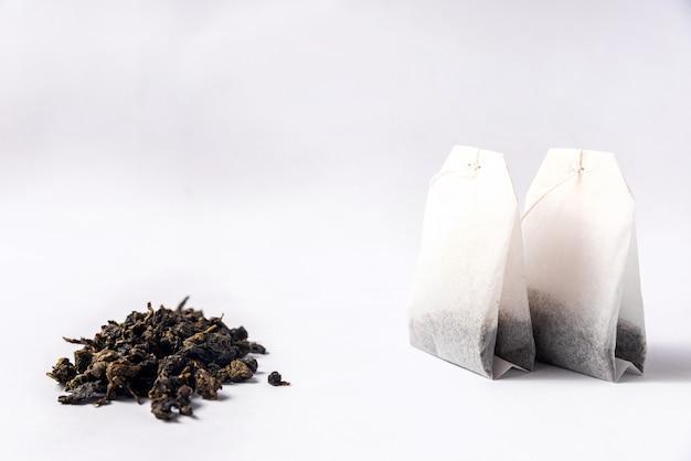 緑のティーバッグと白い背景にルーズな緑茶