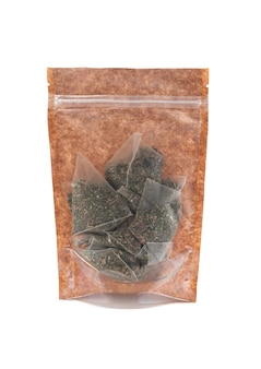 Green tea bags in a brown paper bag. doy-pack with a plastic window for bulk products. close-up. white background. isolated.