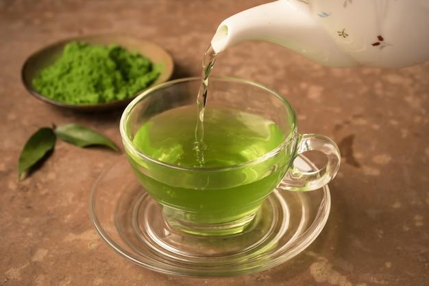 Зеленый чай выливают в стакан чашки чая на стол