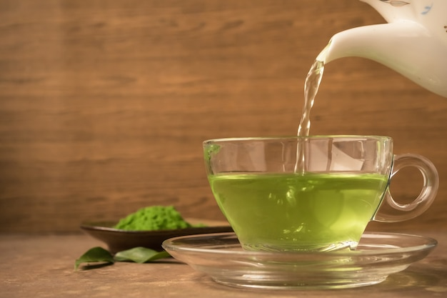 Green tea being poured into glass tea cup on the table