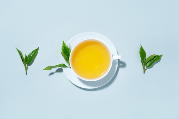 Green tea brewed in cup with tea leaves on blue pastel background. top view.