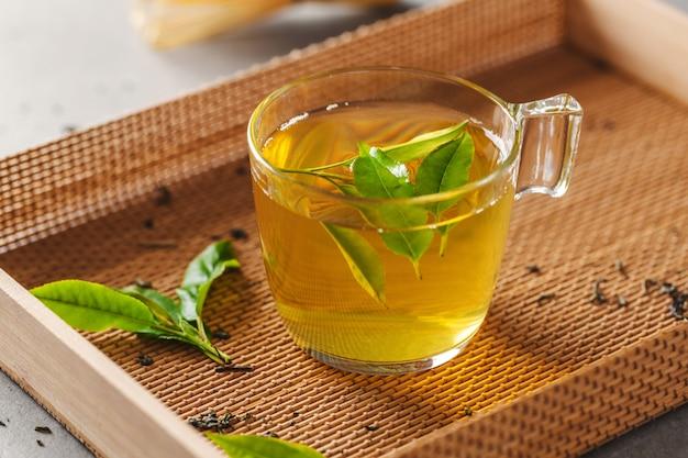 テーブルの上の茶葉とカップで醸造された緑茶。閉じる。