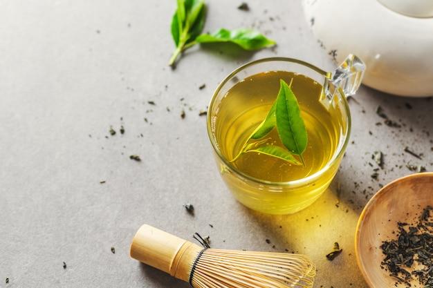 Зеленый чай, сваренный в чашке с чайными листьями на столе. крупный план.