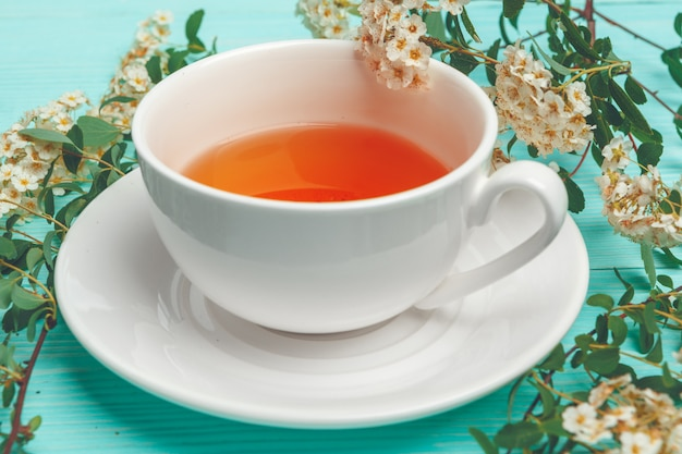 Green tea in a ceramic cup with branches of blossoming tree branches