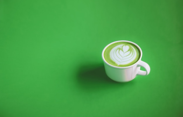 Green tea concept, green tea milk with art on top with white cup on green background