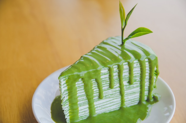 Green tea crepe cake on white plate on wooden table