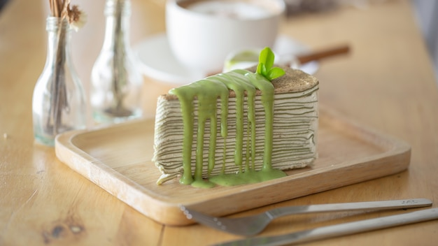 Green tea crepe cake with green tea leaf on wooden plate.